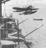Japanese E13A seaplane being craned onto cruiser Kinugasa, 1940s; note Type 10 120mm guns in foreground