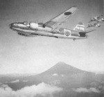 A formation of G4M1 Model 11 bombers in flight with a mountain in the background, date unknown