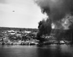 Peleliu, Palau Islands under attack by US Navy carrier aircraft, 30 Mar 1944; note F6F Hellcat fighter in flight