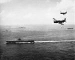 SB2C Helldivers flying over USS Essex during the Okinawa campaign, May 1945; USS Bunker Hill, USS Langley, and other vessels in background
