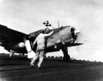 Flight deck officer of USS Hancock directing a SB2C Helldiver aircraft for takeoff, off Philippine Islands, 25 Nov 1944