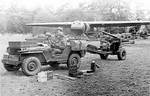 British troops towing a field gun with jeep, with ammunition boxes on the hood, England, United Kingdom, 1944; note Horsa glider in background