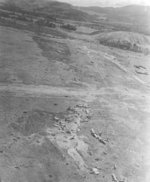 Bomb Damage Assessment photo of destroyed Ki-48 bombers at a Japanese airstrip in northern New Guinea, 1942-1943, photo 2 of 2; note open parachutes in upper center (bombs or supplies?)