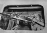US Army combat photographer Staff Sergeant Andrew Yusko, Jr. posing with a M2 0.50 caliber machine gun aboard a B-24 Liberator bomber in Australia, 8 Jul 1944