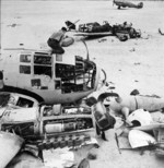 Allied ground crew disassembling a wrecked German He 111 aircraft near Daba and Fuka, Egypt, circa 1942; note wrecked Bf 109 fighter and Hurricane Mk II fighter in background