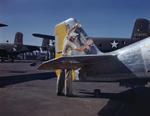 A North American Aviation worker preparing a P-51 Mustang fighter for painting, Inglewood, California, United States, Oct 1942; note B-25 Mitchell bombers in background