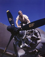 Douglas Aircraft Company employee working on the port engine of a C-47 Skytrain aircraft, Long Beach, California, United States, Oct 1942