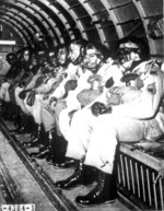16 US Army African-American paratrooper trainees in a C-47 Skytrain aircraft, preparing to make 1 of the 5 qualifying jumps, Fort Benning, Georgia, United States, Mar 1944