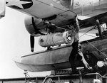 Removing a Mark XVII depth bomb from SOC Seagull aircraft of cruiser Philadelphia, 2 Jul 1942, photo 1 of 2