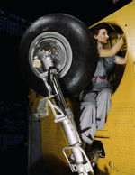 Female employee of Vultee working in the wheel well of a Vengeance dive bomber, Nashville, Tennessee, United States, Feb 1943