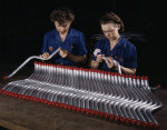 Two female employees of Vultee inspecting tubing that would later be used in Vengeance dive bombers, Nashville, Tennessee, United States, Feb 1943