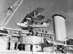 Royal Australian Air Force Walrus aircraft A2-7 being lifted onto a Leander-class light cruiser, 1939