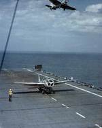 A FM-2 Wildcat fighter prepared to launch from USS Charger while another flew overhead, Chesapeake Bay, Maryland, United States, 8 May 1944