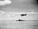 Martlet fighter of No. 888 Squadron FAA from HMS Formidable in flight over the Indian Ocean off Madagascar, late Apr to early May 1942; note HMS Warspite in background
