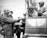 Two French soldiers giving African-American soldiers candy, Rouffach, France, 5 Feb 1945