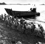 American troops marching up the beach at Adak, Aleutian Islands during pre-invasion loading for the Kiska invasion, 13 Aug 1943; note LCM landing craft, USS Pennsylvania, and M1 Garand rifles