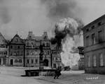 Men of US 101st Infantry Regiment running past a burning fuel trailer in square of Kronach, Bayreuth, Germany, 14 Apr 1945