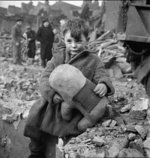 Abandoned boy holding a stuffed toy animal amid ruins following German aerial bombing of London, England, United Kingdom, 1940