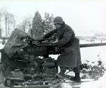 Pvt Paul Romanick of Battery B, 103rd Anti-aircraft Artillery Battalion, US 1st Infantry Division cleaning 40mm anti-aircraft gun, Sourbrodt, Belgium, 31 Dec 1944; note 6 swastika symbols his 6 kills