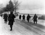 Troops of US 101st Airborne Division moving out of Bastogne, Belgium, 31 Dec 1944