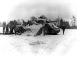 US 5th Armored Regiment tankers gathering around a fire and opening Christmas presents, near Eupen, Belgium, 30 Dec 1944; note M4 Sherman tank