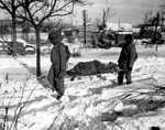 Two US Army African-American soldiers carrying the body of another American soldier near Malmédy, Belgium, circa 17 Dec 1944