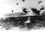 Lexington under attack during Battle of Coral Sea, photographed by a Japanese pilot, 8 May 1942; destroyer Phelps at bottom of photo