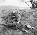 Two young German soldiers, one injured, the other dead, east of the Rhine River, Germany, late Mar 1945