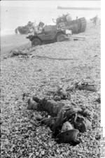 Remains of a Canadian soldier on the beach after the failed raid on Dieppe, France, Aug 1942; note Daimler Scout Car and Churchill tank in background