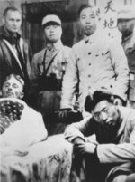 A wounded Doolittle raider lying in a cot, surrounded by John Hilger and Chinese military presonnel, China, Apr 1942