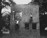 Two Operation Jedburgh personnel scaling a brick wall in training, Milton Hall, Cambridgeshire, England, United Kingdom, circa 1944