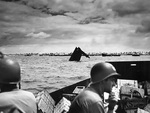 US Coast Guard personnel transporting supplies to Tarawa, Gilbert Islands, circa 20-23 Nov 1943; note the wreck of an American LCVP in center of photo