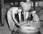 US personnel checking an atomic bomb casing, Tinian, Mariana Islands, 1945