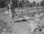 A German woman covering her nose and mouth as she walked by the 800 exhumed bodies of forced laborers murdered by SS men, near Nammering, Germany, 17 May 1945