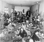 Women and children, former inmates of Bergen-Belsen Concentration Camp, huddled together in a large room after liberation, Germany, 17-18 Apr 1945