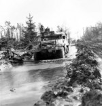 M3 Half-track vehicle of 16th Infantry Regiment, US 1st Infantry Division moving through a muddy road in the Hürtgen Forest, Germany, 15 Feb 1945