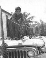 Japanese-American soldier of US 442nd Regimental Combat Team hanging laundry on a jeep in such a way that the vehicle could still be operated in urgent situations, Castellina Sector, Italy, 12 Jul 194
