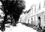 Japanese-American troops of 100th Infantry Battalion of US 442nd Regimental Combat Team resting on the side of a street in Livorno, Castellina Sector, Italy, 19 Jul 1944