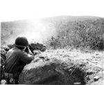 Japanese-American soldier of 100th Infantry Battalion, US 442nd Regimental Combat Team firing at a suspected German sniper position, Montenero area, Italy, 7 Aug 1944