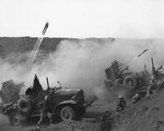 US Marine rocket-launching trucks in action on Iwo Jima, Japan, 28 Feb 1945; note Mk 7 rocket launcher firing 4.5-inch beach barrage rockets