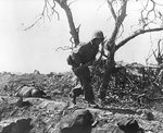 A US Marine ran past a dead Japanese soldier, Iwo Jima, Japan, 3 Mar 1945