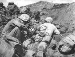 US Navy Corpsman dressed a back wound of a Marine who was hit by the enemy in the battle on Iwo Jima, Feb 1945