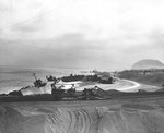 An American bulldozer pulled a road grader on an Iwo Jima beach, 21 Apr 1945, note several Japanese landing ships wrecked on the coast beyond the road