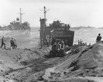 A bulldozer preparing a roadway as LSM-47 opened her cargo bay doors, Green Beach, Iwo Jima, Japan, circa 25 Feb 1945