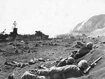 US Marines burrowing in the volcanic sand on the beach of Iwo Jima, Japan, 20 Feb 1945; note LST-264 and Mount Suribachi in background