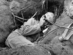 Burrowed in his shallow foxhole at the edge of Motoyama airstrip on Iwo Jima, an US Marine communicator called for artillery support, Feb 1945