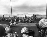 Men of the US 4th Marines rushing out of their landing craft for Iwo Jima landing beach, 19 Feb 1945, photo 1 of 2; note LVT burning in right center