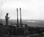 Overlooking Motoyama Airfield, Iwo Jima, Japan, 4 Mar 1945; note US Marine with M1 Carbine, Type 96 anti-aircraft mount, and the first B-29 to land on Iwo Jima
