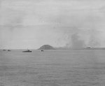 Minesweepers worked the waters off Iwo Jima before the invasion, 17-18 Feb 1945; note the anti-aircraft bursts above the island and a burning aircraft close to the ground on the right