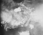 Smoke rising from Mount Suribachi as it was hit by aerial bombs and naval guns, 19 Feb 1945